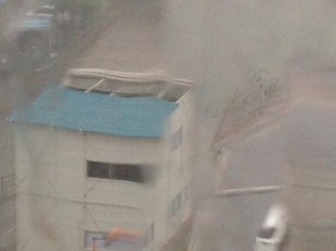 ホテルの窓から見えた工事現場では、プレハブの事務所の屋根が風でめくれ上がっていた。