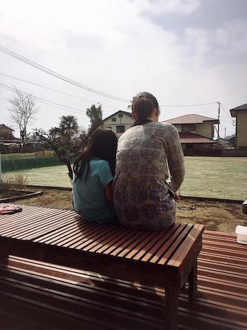 庭の畑仕事を終え、ウッドデッキで休憩する妻と娘