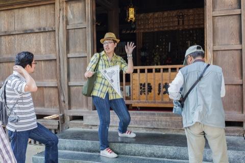 お堂の中の仏像について説明する青木さん。
