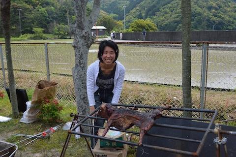 田植えの後のバーベキューで獲物のイノシシを振る舞う乃一さん。